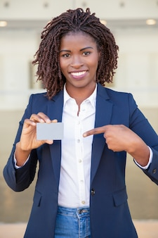 Happy confident businesswoman showing id card