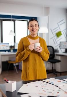 Счастливая уверенно жизнерадостная женщина, смотрящая на камеру в офисе компании запуска, держа чашку кофе. исполнительный предприниматель, руководитель-менеджер, постоянно работающий над проектами.