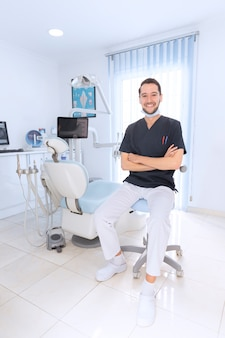 Happy confident dentist in clinic
