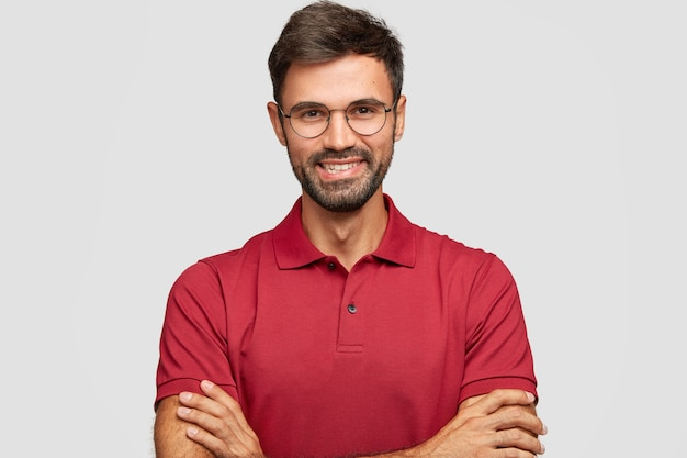 Happy confident male entrepreneur with postive smile, has beard and mustache, keeps arms folded, being in high spirit after successful meeting with partners, poses against white wall, dressed casually