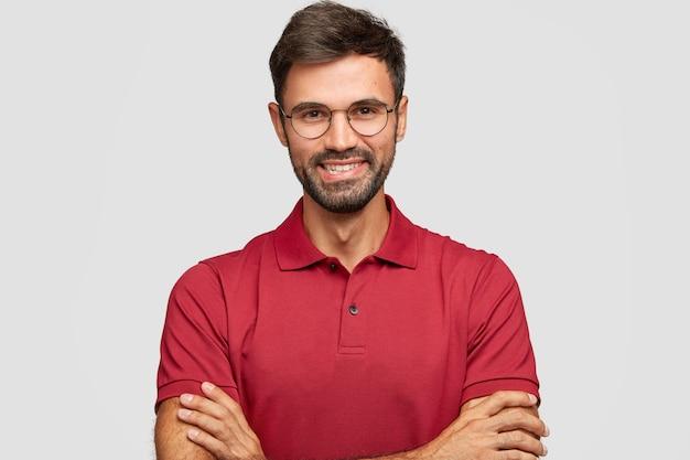 Felice imprenditore maschio fiducioso con un sorriso postivo, ha barba e baffi, tiene le braccia conserte, è di buon umore dopo un incontro riuscito con i partner, posa contro il muro bianco, vestito casualmente