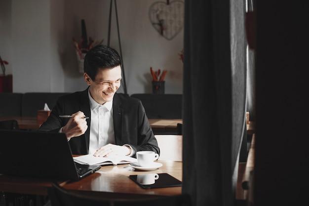 笑顔で目をそらし、ノートブックを操作しながら勝利を表現する手で成功のジェスチャーを示す幸せな自信のあるマネージャー。