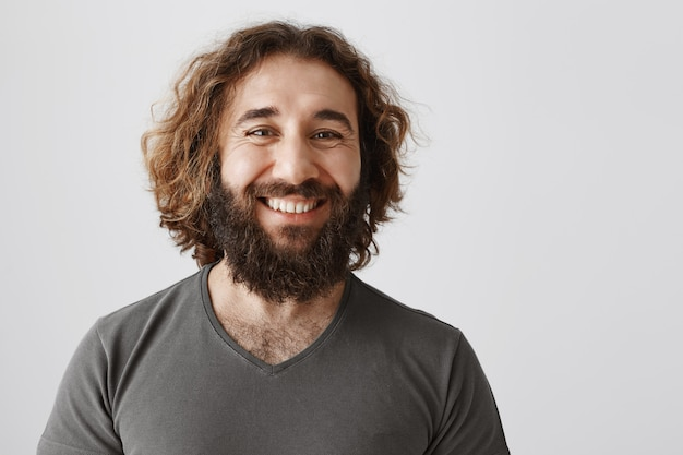 Счастливый уверенный ближневосточный мужчина улыбается с белыми зубами