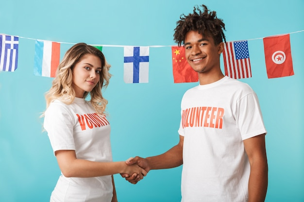 Happy confident multiethnic couple wearing volunteers t-shirt standing isolated over blue wall, shaking hands
