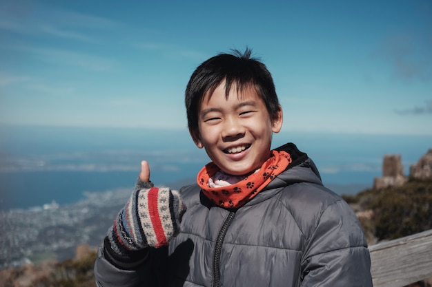 Happy and confident tween mixed race asian boy smiling and giving thumb up over mountain view