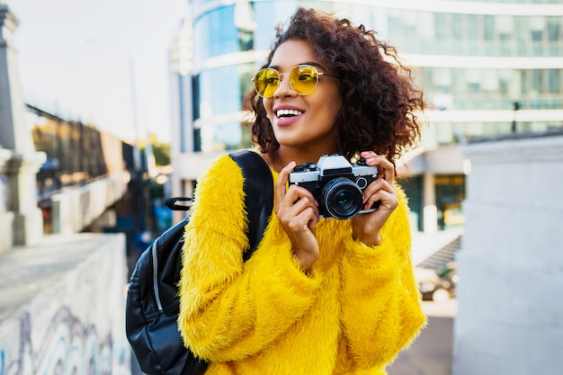 Happy confident  woman holding photo camera and walking in big modern city. +