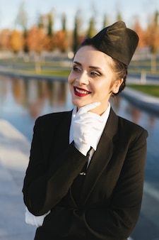 Happy confident woman stewardess in uniform thinks about the sky