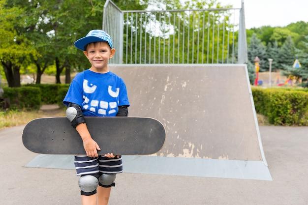 カメラに微笑んで彼の腕の下でそれを保持している彼のスケートボードがランプのふもとに立っている幸せな自信を持って若い男の子
