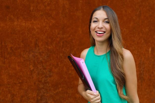 ラッシュの背景に屋外のカメラを見て幸せな自信を持って若いビジネス女性。コピースペース。