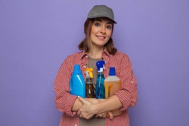 Felice e fiduciosa giovane donna delle pulizie in camicia a quadri e berretto con bottiglie di prodotti per la pulizia guardando la telecamera con un sorriso sul viso in piedi su sfondo viola