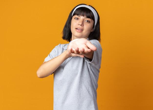 Felice e fiduciosa giovane ragazza fitness che indossa una fascia che allunga le mani pronte per l'allenamento in piedi sopra l'arancia