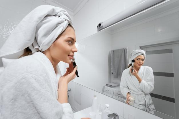 Счастливая уверенная молодая дама с полотенцем на голове делает макияж