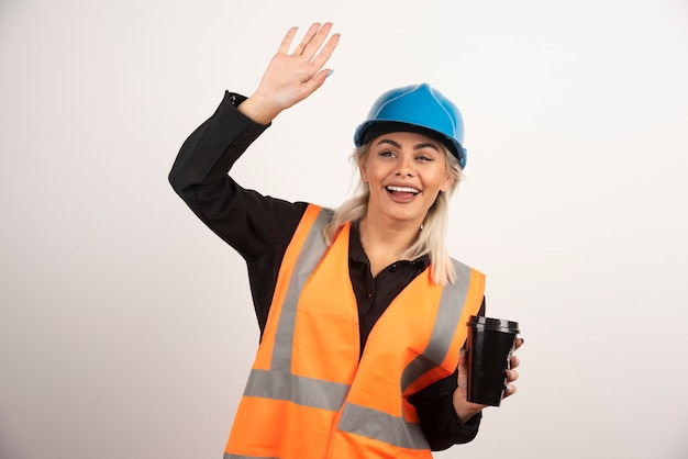 Happy construction with cup of tea waving someone. high quality photo