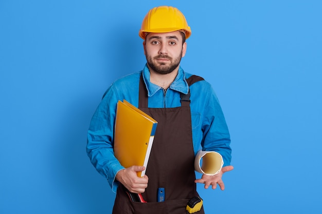 Happy construction worker guy holding paper folder, looks at camera with puzzles facial expression, wearing uniform? brown apron and yellow helmet, bearded foreman.
