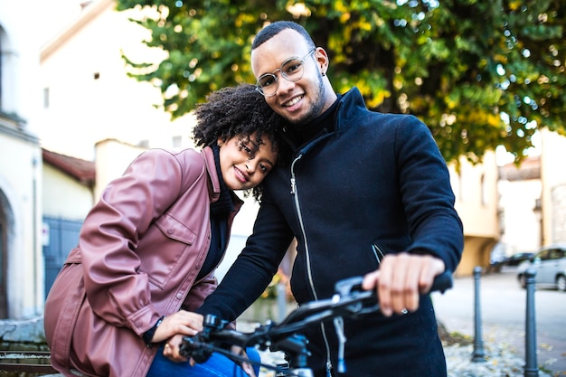 Happy and content black ethnic couple sitting on bicycle.