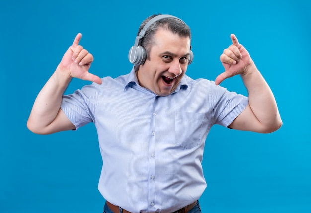 Happy and content middle-aged man in blue striped shirt in headphones raising hands on a blue space