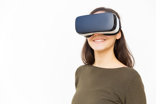 Happy content woman in vr headset smiling at camera