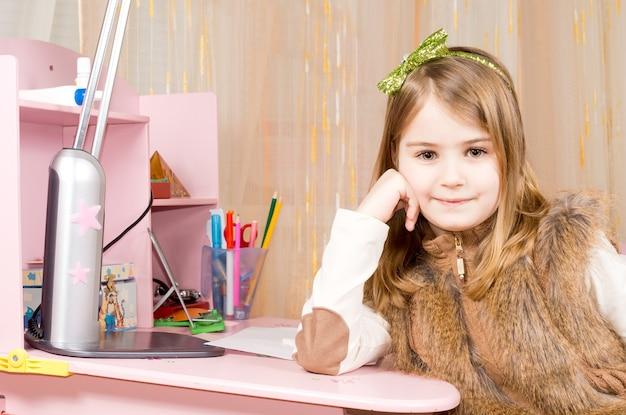 寝室のピンクの机に座って、笑顔でカメラを見ながら手に頭をもたせてリラックスしている幸せな満足の少女