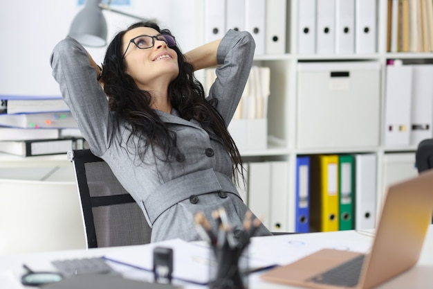 Счастливая довольная женщина, отдыхающая в офисе, сидит с ноутбуком и держит руки за завершением головы