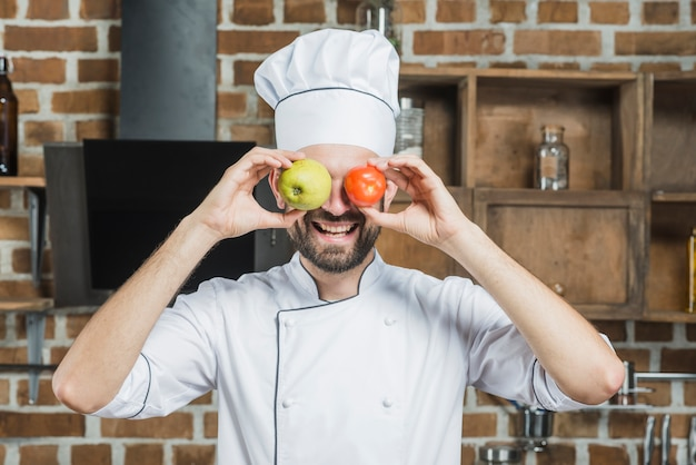 Happy cook holding apple and red tomato in front of his eyes