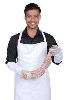 Happy cook holding sausage and smiling.