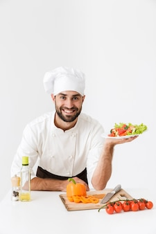 Happy cook man in uniform smiling and holding plate with vegetable salad isolated over white wall