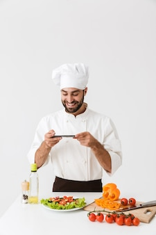 Happy cook man in uniform smiling and taking photo of plate with vegetable salad on smartphone isolated over white wall