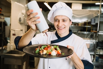 Happy cook pouring sauce on plate with salad