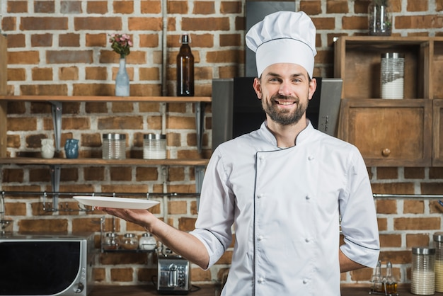 Happy cook wearing chef's hat holding an empty plate in hand