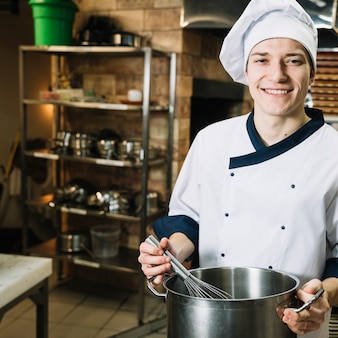 Happy cook whipping something in pot with whisk