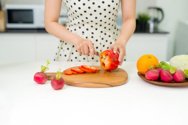 幸せな料理。台所でサラダのために野菜を切る若いアジアの女性