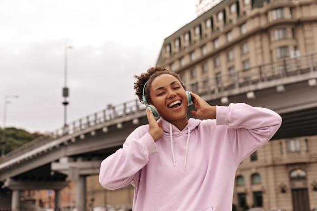 세련된 분홍색 후드티를 입은 행복한 곱슬머리 갈색 머리 여성은 야외에서 헤드폰으로 노래를 부르고, 웃고, 음악을 듣습니다.