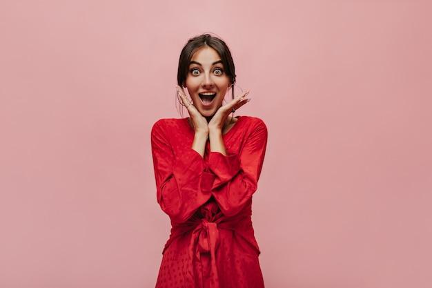 액세서리에 검은 머리를 하고 카메라를 쳐다보고 분홍색 벽에 기뻐하는 아름다운 물방울 무늬 밝은 드레스를 입은 행복한 멋진 여성