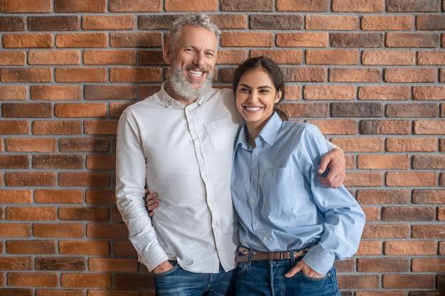 행복한 커플. 벽돌담 옆에 서서 아내를 껴안고 있는 백발의 남자