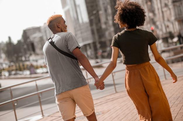 幸せなカップル。興奮している通りの幸せな浅黒い肌のカップル