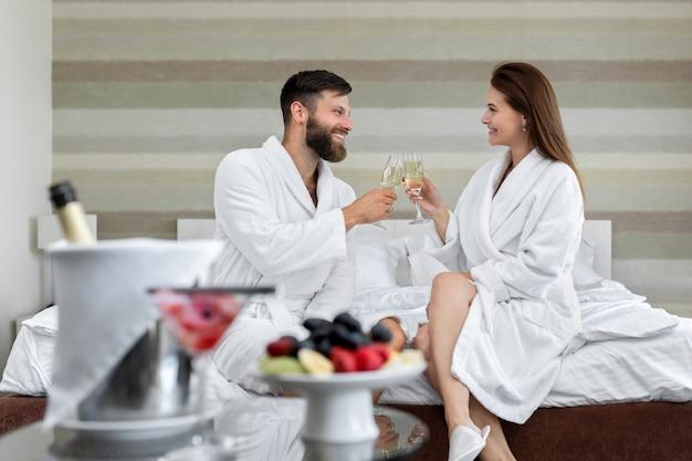 행복한 커플 한 남자와 흰 코트를 입은 여자가 서로 미소를 짓고 호텔 방의 침대에서 스파클링 와인을 마신다.
