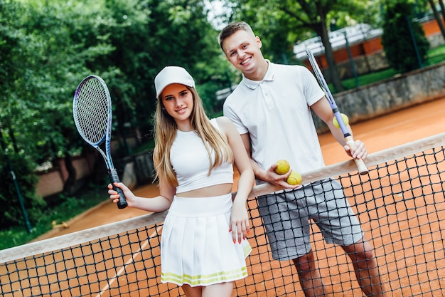 Happy couple after playing tennis on court. portrait of smiling young man and beautiful woman with tennis rackets.