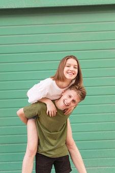 Happy couple against the of a colored green wall, the boy holds the girl on her back
