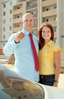 Happy couple against real estate