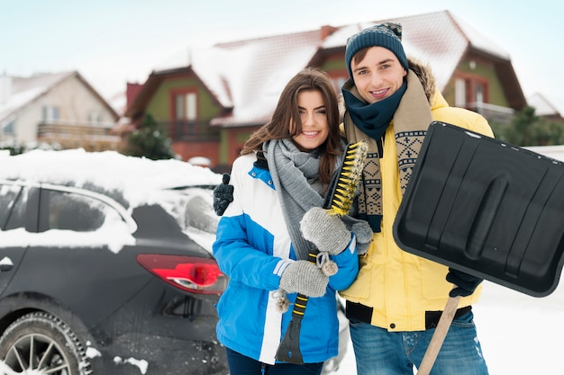 Happy couple are ready to cleaning car from snow