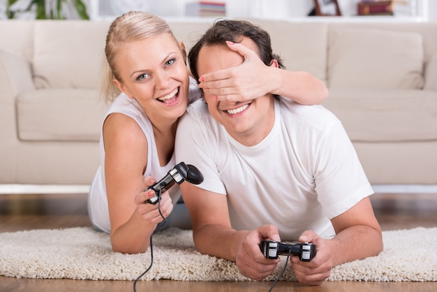 Happy couple are spending time together with video game.