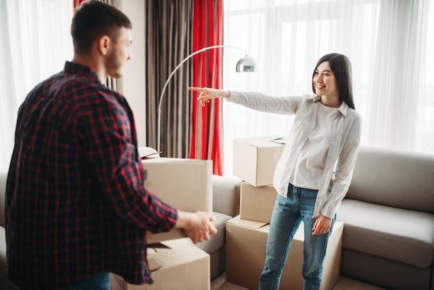 행복 한 커플은 새 집으로 이동하는 방에 골 판지 상자를 정렬합니다. 포장 된 아파트로 이전