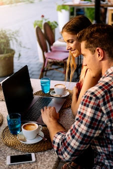 ラップトップを使用してコーヒーショップで幸せなカップル。実際のライフスタイルの概念。
