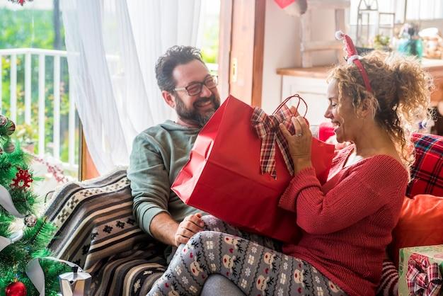 집에서 행복한 커플은 함께 크리스마스 이브를 즐길 선물을 공유 웃고 집에서 휴가 시즌을 축하