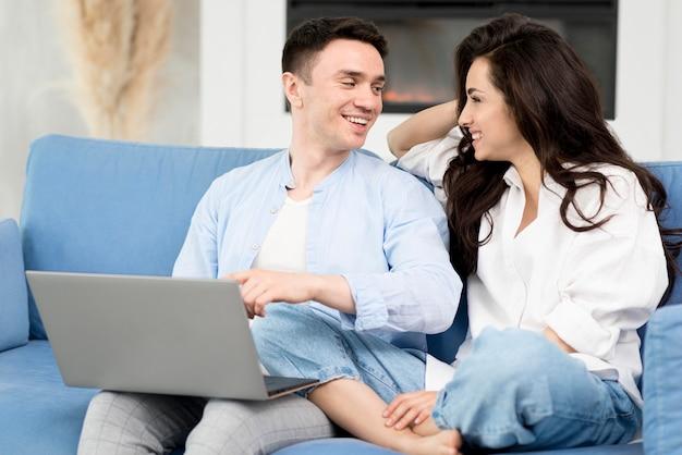 自宅のラップトップが付いているソファーで幸せなカップル