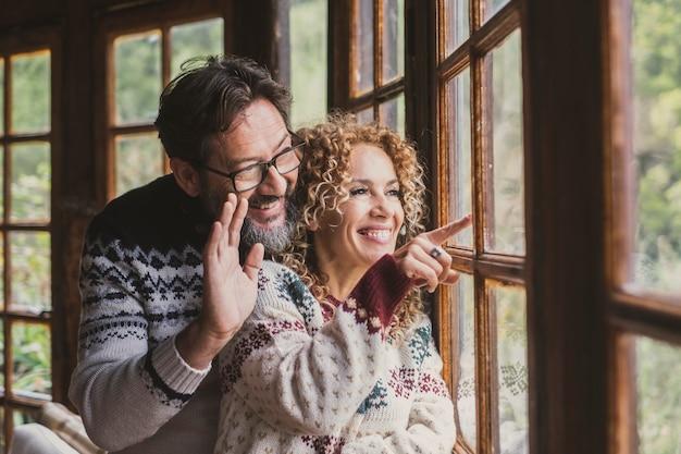 友達がクリスマスを祝うのを待っている家で幸せなカップル
