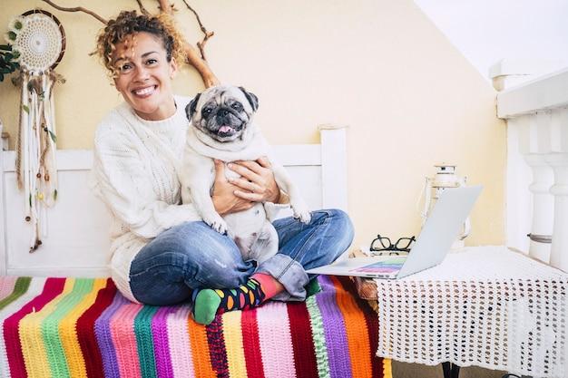Счастливая пара дома с красивой женщиной среднего возраста и забавной собакой мопсом
