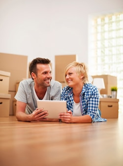 Счастливая пара в новой квартире с цифровым планшетом