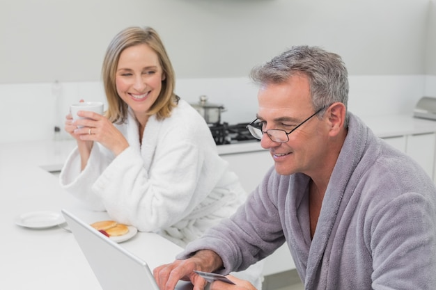 Happy couple in bathrobe doing online shopping at home