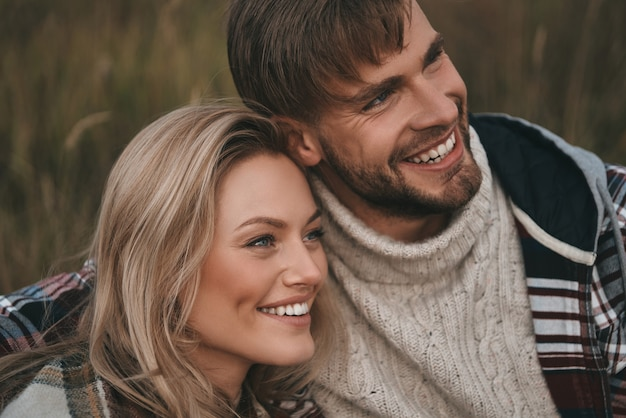 Счастливая пара. красивая молодая пара обнимая и глядя с улыбкой, сидя на поле